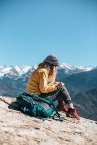Travel copywriting - image of woman on mountain with journal